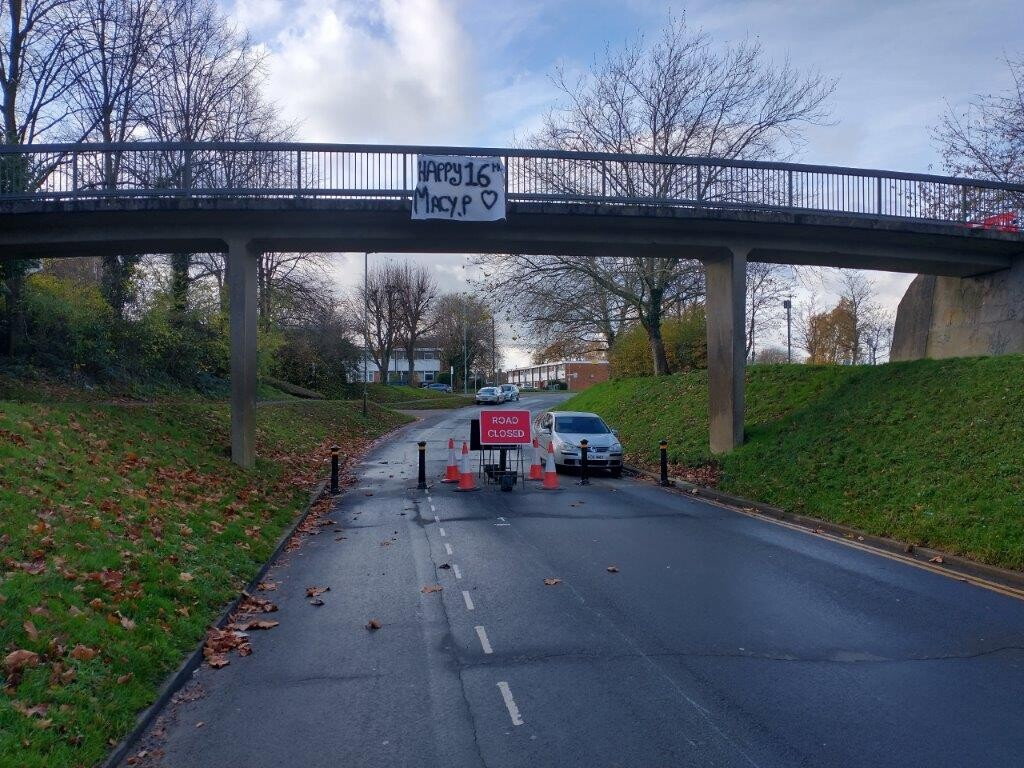 Link Drive in Hatfield showing bollards placed accross the road under the pedestrian bridge to prevent use by cars, but keeping the road open for cycling.