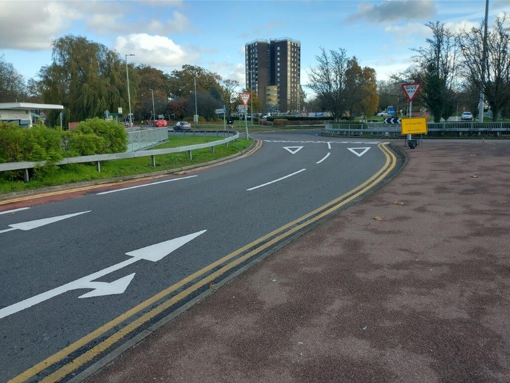Queensway Hatfield looking north towards the roundabout junction with Woods Ave showing the faded non-mandatory cycle lane joining the roundabout.