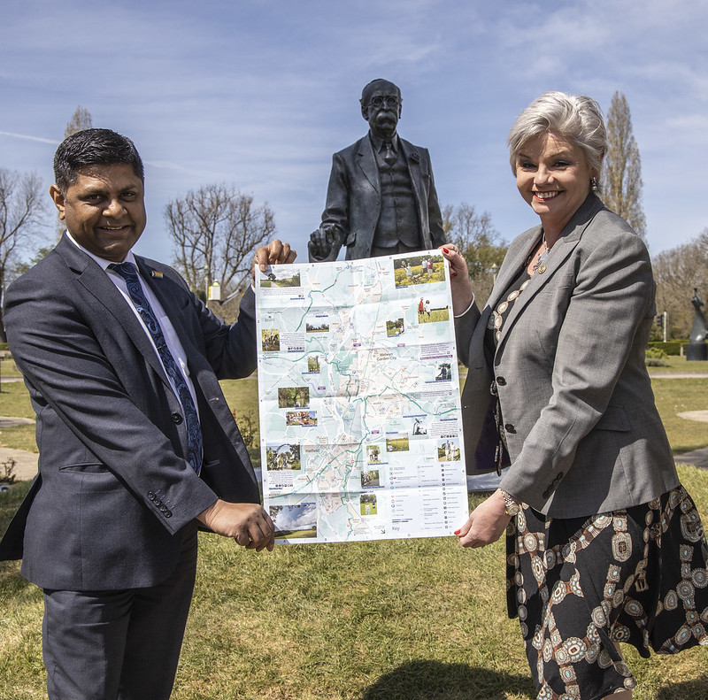 OJ Daya (Waitrose WGC) and Claire Austin (Austin's Funeral Services) holding up the open map in front of the Ebenezer Howard statue, Welwyn Garden City